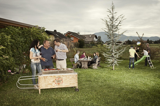 Family and friends haveing a barbecue party with La Caja China pig roaster.