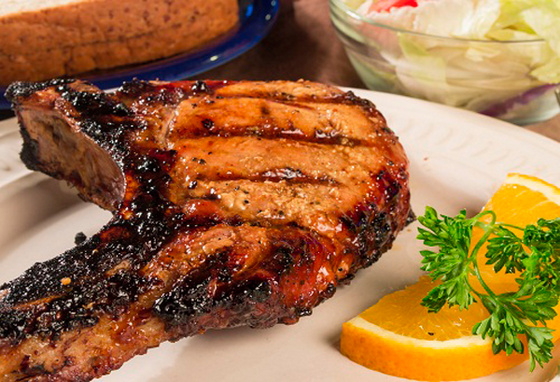 Grilled pork chop on La Caja China roasting grill.