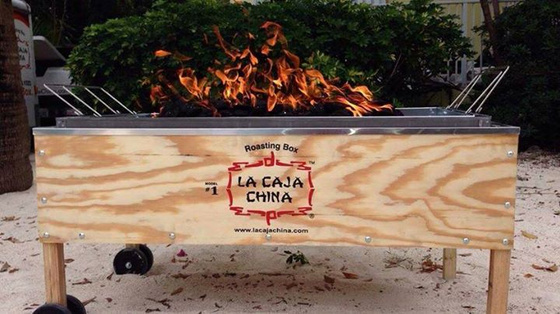 La Caja China roasting box with hot coals on fire in nature.